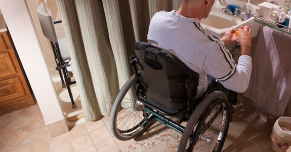 Man uses wheelchair in bathroom remodeled for accessibility
