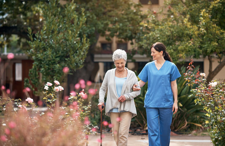 Woman walks in a garden with assistance from caregiver