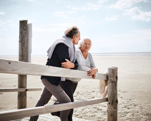 Retired couple leaning on a fence at the beach