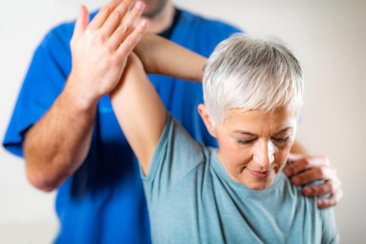 A chiropractor pulls a woman's arm back in a stretch