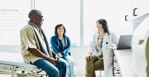 Doctor speaks with smiling couple in doctor's office