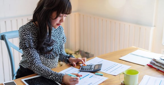 Woman using calculator to determine costs