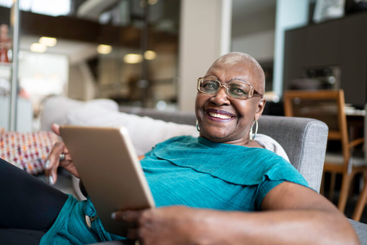 Happy woman smiles while using tablet at home