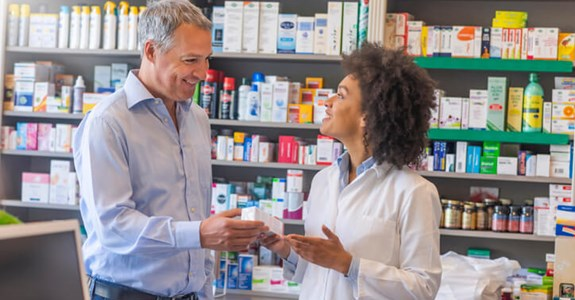 Smiling pharmacist helping customer at pharmacy
