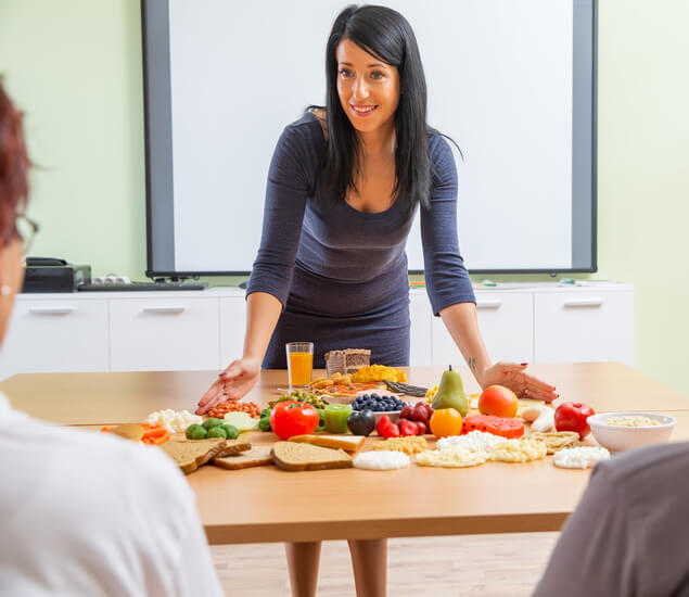 Nutritionist dietitian lays out healthy foods on table for clients