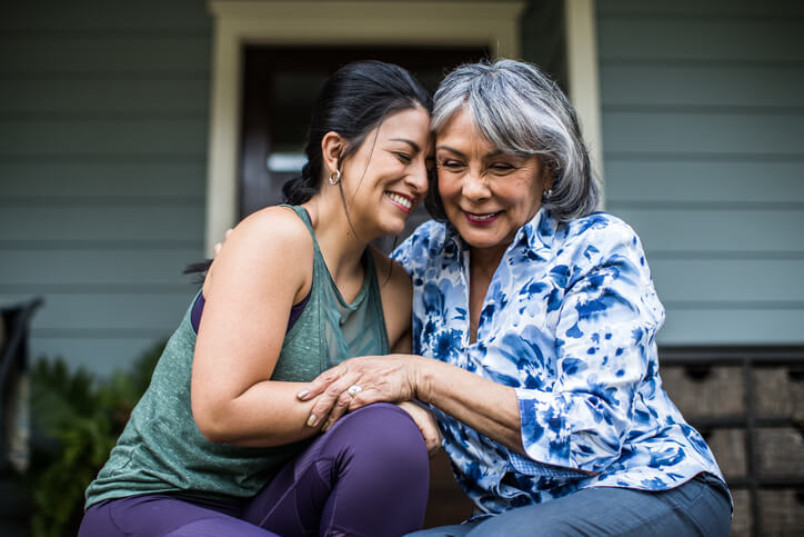 Woman and adult daughter embrace and smile while sitting on home front steps