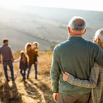 Grandparents Embrace And Gaze At Family