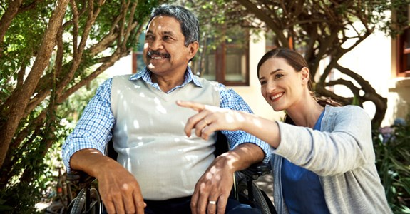 Caregiver points to something while spending time outside with patient