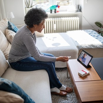 Woman at home speaks with doctor using telemedicine