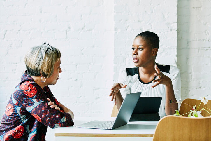 Two women chat while one uses her laptop computer