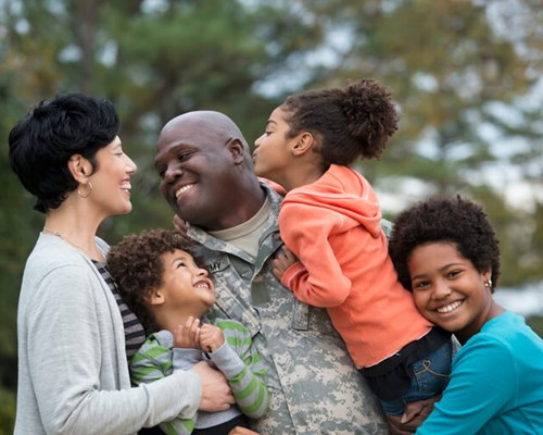 Veteran father smiles and embraces his children