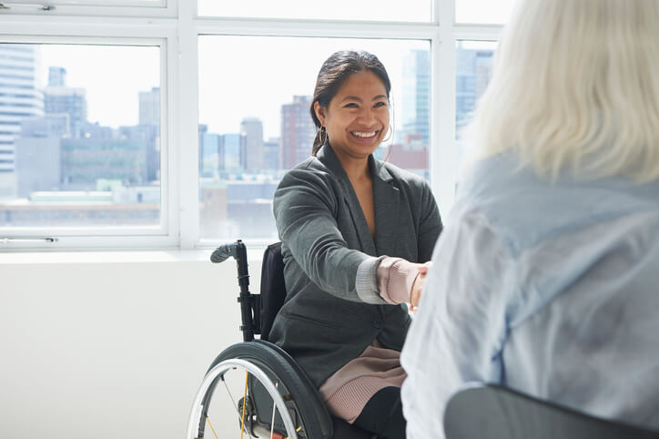 Woman in wheelchair smiles and shakes hands with another woman
