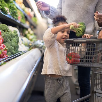 Girl Puts Produce In Grocery Cart