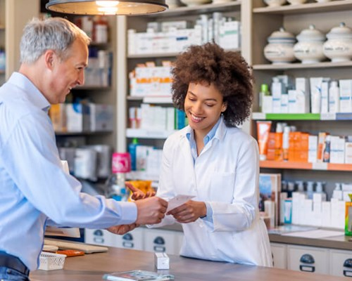 Pharmacist gives prescription to patient at drug store