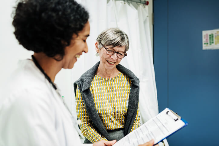 Smiling doctor reviews medical information with happy patient
