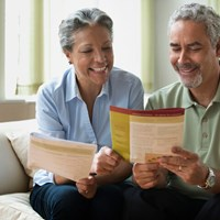 Smiling couple at home reviewing insurance information