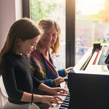 Smiling grandmother teaches granddaughter to play piano