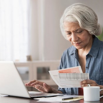 A woman uses her computer while reviewing paper copies of bills