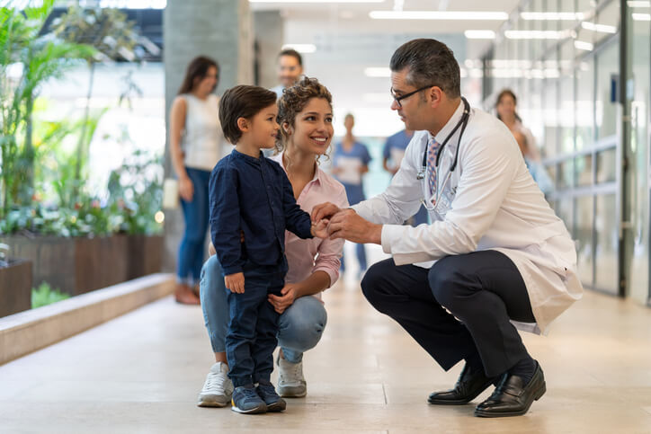 A doctor crouches to speak with young boy and his mother