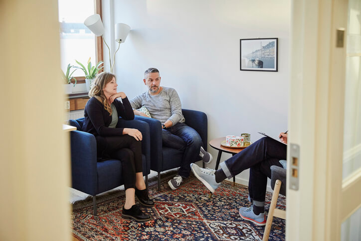 A couple sit on cushioned chairs while speaking with a therapist