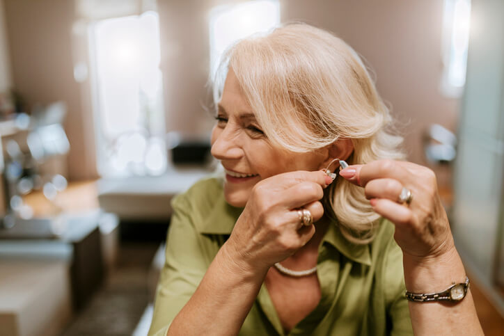 Woman smiles and fits on her hearing aids