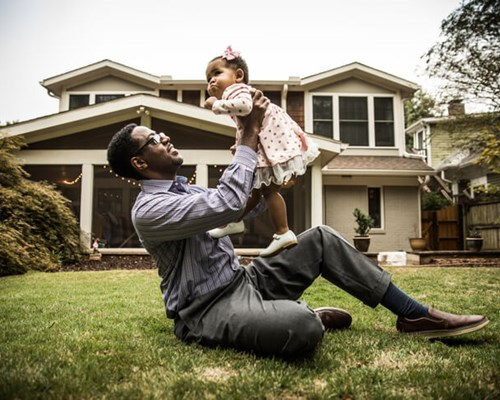Father holds up his infant daughter while sitting on front lawn
