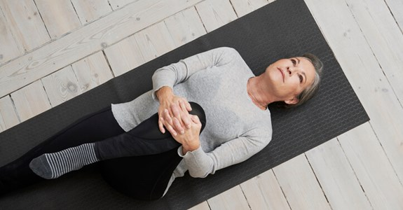 A woman lays on a yoga mat and stretches